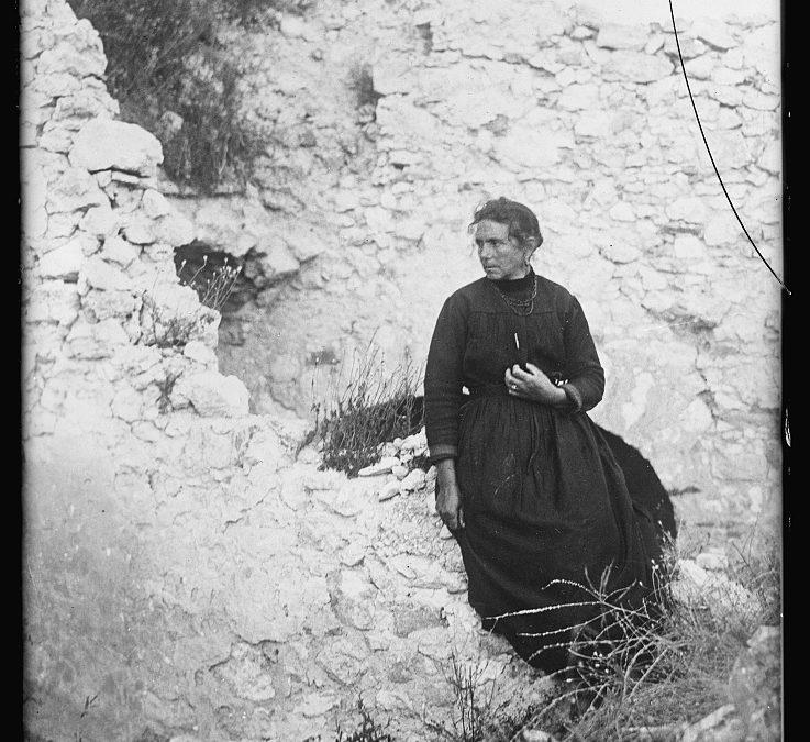 Una donna di Avezzano accanto a ciò che rimane della sua casa
