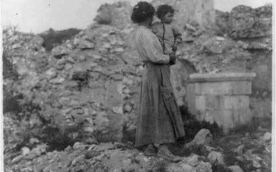 Una donna tiene in braccio suo figlio tra le macerie